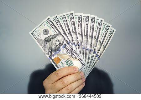 Hands Holding Dollar Cash. 1000 Dollars In 100 Bills In A Mans Hand Close-up On A Dark Background.