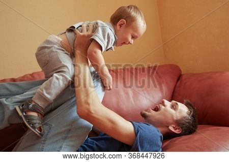 Happy Playful Handsome Caucasian Young Father Playing With Baby On Sofa In Living Room At Home. Funn