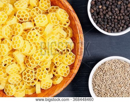 Raw Pasta In A Bamboo Bowl And Spice Black Pepper, Cumin (jeera) On Black Wooden Background. Healthy