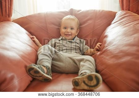 Cute Cheerful Shy Toddler Child Lying In Comfortable Big Red Leather Armchair Home Portrait. Smiling