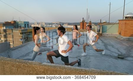 Fitness, Sport, Friendship And Healthy Lifestyle Concept. Group Of Friends Exercising Outdoor