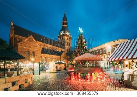 Riga, Latvia. Christmas Market On Dome Square With Riga Dome Cathedral. Christmas Tree And Trading H