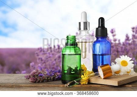 Bottles Of Essential Oils And Wildflowers On Wooden Table Against Blurred Background. Space For Text