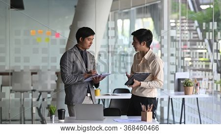 Photo Of Young Business Consulting Man While Talking/giving An Advice To Young Professional Man.