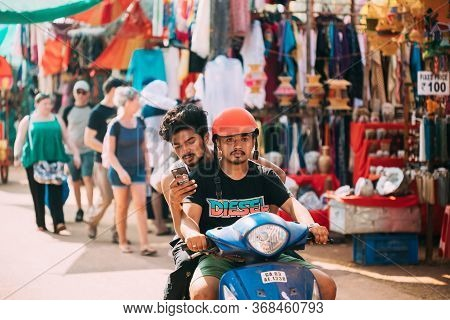 Anjuna, Goa, India - February 19, 2020: Men Riding On Scooter Motorcycle In The Anjuna Market.