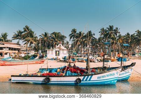 Mapusa, Anjuna, Goa, India - February 19, 2020: Fishermen Resting Near Pulled Boat From Sea