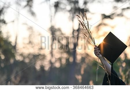 Photo Of Graduate Woman Hand Holding The Graduation Cap And Wild Grass In Hand. Graduation Celebrati