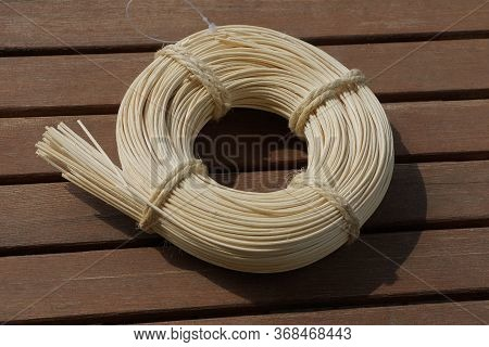 A White Twine In A Round Skein For Decoration Decor Lies On A Brown Wooden Table