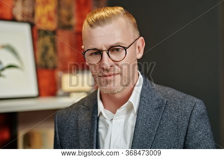 Portrait of a respectable middle-aged businessman in elegant suit and spectacles standing at his office. Business style. Optics for men.
