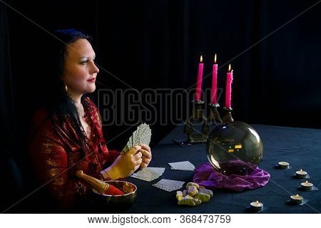 Young Clairvoyant And Fortuneteller With Cards In Hands In A Magic Salon On A Black Background.
