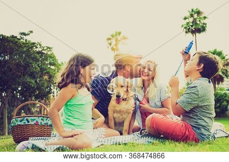 Mother, Father, Sons And Their Dog In A Happy Summer Time Laughing, The Boy Playing With Soap Bubble