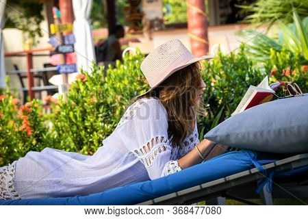 Beautiful Woman Relaxing In Vacation. Beautiful Woman Reading Book In Vacation. Happy Beautiful Woma