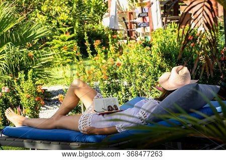 Beautiful Woman Relaxing In Vacation. Beautiful Woman Reading Book In Vacation. Happy Beautiful Woma