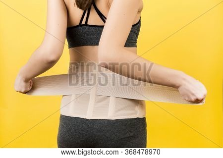 Back View Of Pregnant Woman Dressing Orthopedic Corset To Make The Backache Go Away At Yellow Backgr