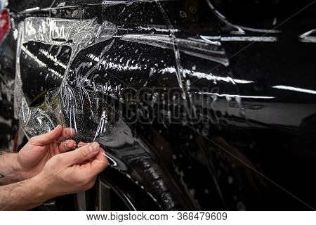 Car Wrappping. Man Car Detailing Studio Worker Appling Transparent Protection Foil On Car Body.
