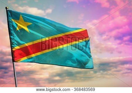Fluttering Democratic Republic Of Congo Flag On Colorful Cloudy Sky Background. Democratic Republic