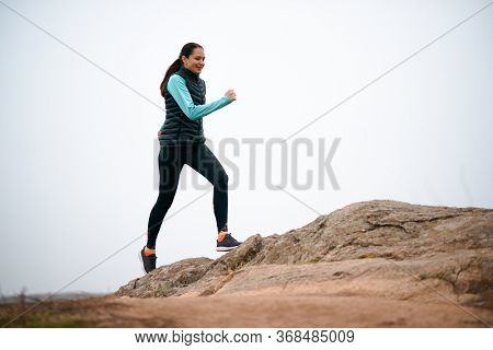 Beautiful Smiling Woman Running on the Mountain Trail at Cold Autumn Evening. Sport and Active Lifestyle Concept.