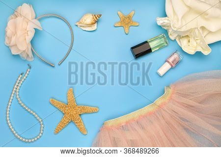 Children's Summer Clothing And Accessories On A Blue Background. Top View.