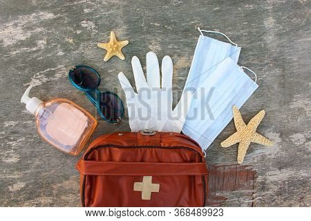 First Aid Kit On Old Wooden Background. Concept Of Protect Yourself From Covid-2019 In Journey. Top