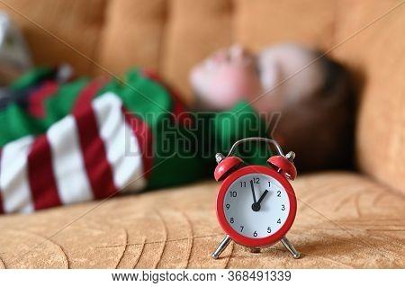 Babys Daytime Sleep. Lunch Baby Sleep. The Red Clock Shows The Babys Sleep Time.