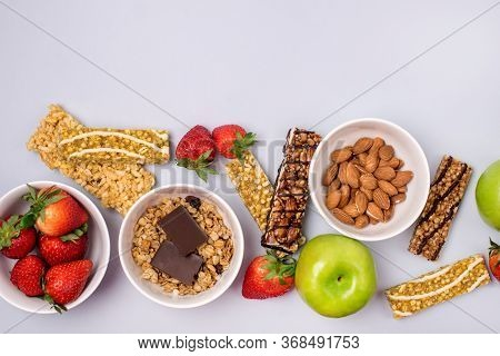 Bowls With Granola Or Muesli Bowl With Strawberry And Almond Muesli Bars Green Apples Blue Backgroun