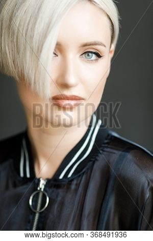 Portrait Of A Fashion Blonde With Short Hair And Wearing A Black Jacket On The Background Of Grey Wa