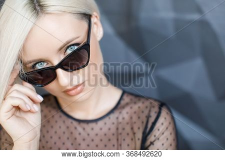 Stylish Blond Woman With Short Hair Cut In Trendy Sun Glasses. Beauty Blond Woman With Blue Eyes In