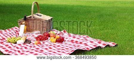 Picnic Basket With Products And Bottle Of Wine On Checkered Blanket In Garden, Space For Text. Banne