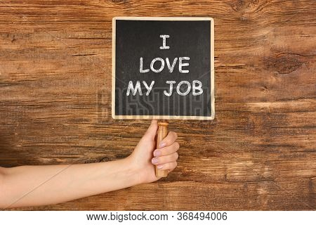 Employee Engagement Concept. Woman Holding Chalkboard With Text I Love My Job On Wooden Background,