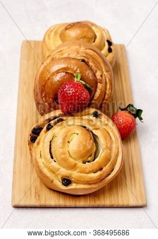 Freshly Baked Buns With Raisins And Cinnamon Decorated With Strawberry On Wooden Tray Light Gray Bac