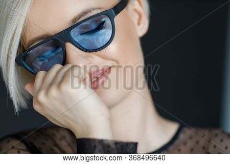 Dreaming Blond Woman With Short Hair Cut In Trendy Sun Glasses With Black Background. Beauty Blond G