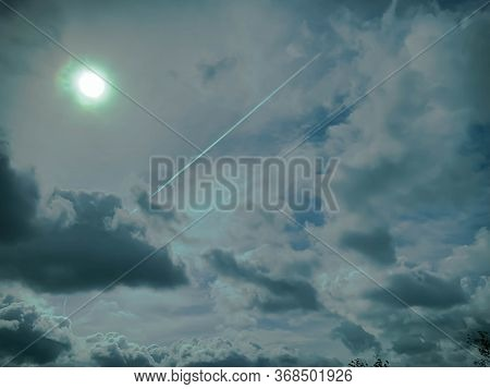 Plane contrails on a dramatic cloudy sky with bright sun in the sky.