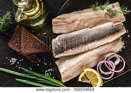 Marinated Fillet Mackerel Or Fillet Herring Fish With Spices, Greens And Slice Of Bread On Plate Ove