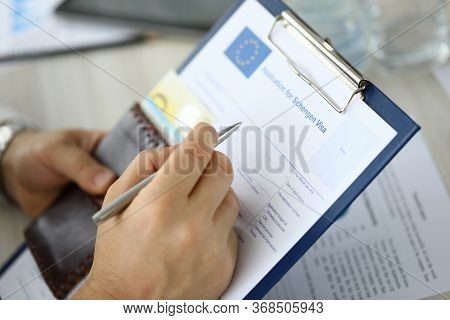 Close-up Of Person Filling Application Form For Schengen Visa On Clipboard. Man Holding Silver Pen.