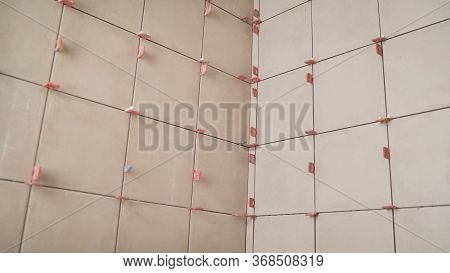 Industrial Worker, Handyman Installing Small Ceramic Tiles On Bathroom Walls. A Small Tile In The Ba