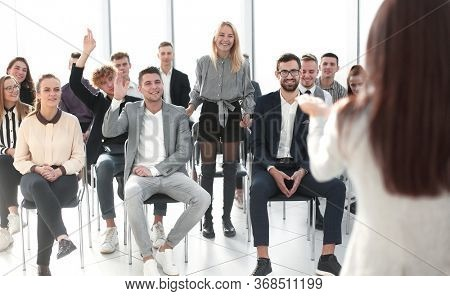 business woman answering questions from employees during a briefing