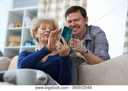 Portrait Of Cheerful Son And Mother Watching Old Photos On Smartphone. Smiling Elderly Woman And Mid