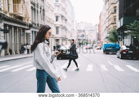 Woman Crossing Street And Messaging On Smartphone