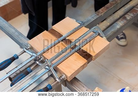 Three Wooden Bars Are Glued To Each Other At Woodwork. Wood Pieces Fixed By Jaws Vise Tongs.