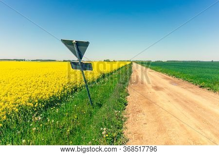 Road Sign Of A Main Road On The Edge Of A Dirt Road In A Field. The Alternation Of Triangles Violate