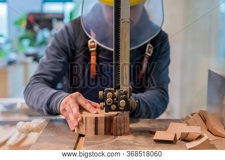 Carpenter Is Cutting The Wooden Piece By Equipment On Stand. The Man's Hand Is Making A Round Detail