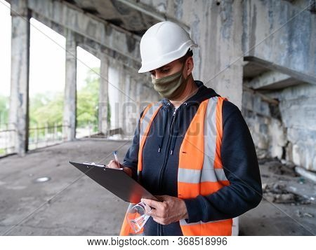 An Engineer At A Construction Site In A Construction Helmet And Medical Mask Records Construction Da