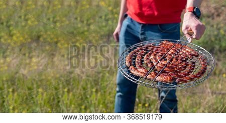 Man Holding Grilling Basket With Roasted Sausages. Grilling Sausages On Barbecue Grill. Bbq Outside.