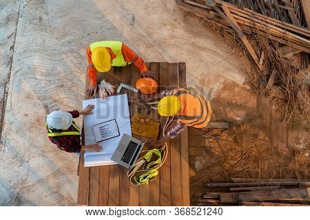 Aerial View Of Group Of Asian Engineers Or Architect And Construction Worker At Construction Site.
