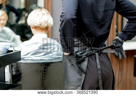 Female Hairdresser Ties Up Apron In Preparation For A Haircut. Toned.