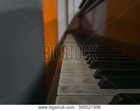 Old Unused Piano Standing Next To Gray And Orange Wall