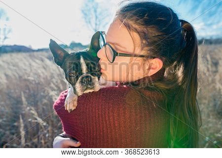 Portrait Of Girl Hugging A Puppy Boston Terrier Dog On Nature Background