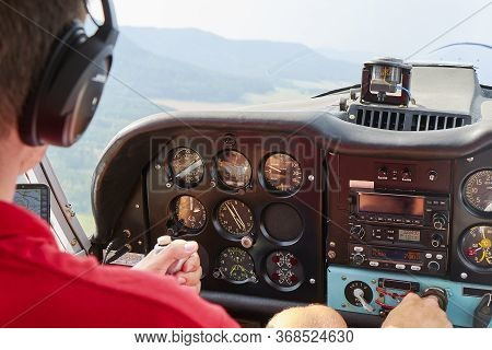 Close Up Of A Man In A Cockpit Piloting Small Four Seat Airplane With Hills And Meadows In A Distanc