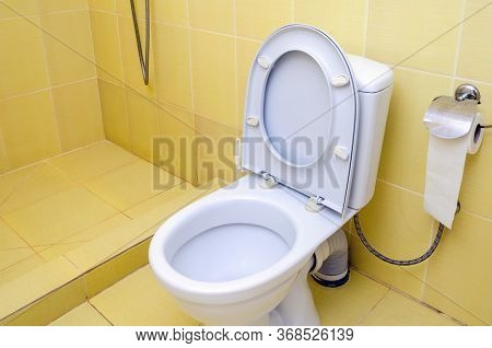 White Toilet And Toilet Paper In The Bathroom.