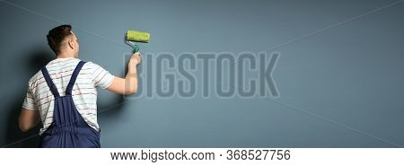 Professional Decorator With Paint Roller Near Grey Wall, Space For Text. Banner Design